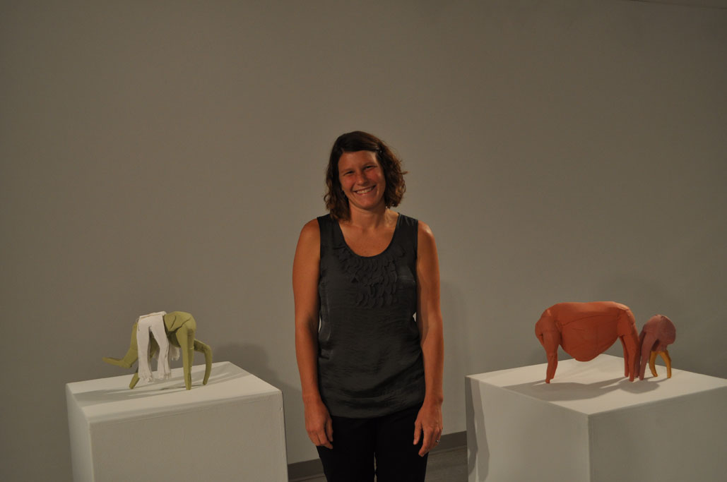 Artist Claire Hedden poses with tow of her many sculptures at her Vignettes opening in the Visual Arts Gallery. The primary material for Hedden's sculptures is clay. She also incorporates other materials, such as fabric, cardboard, and foam into her work.