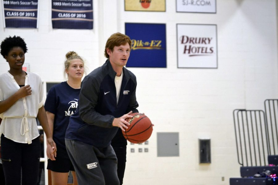 Tennis player Parker Featherston shoots a basketball during Blue Madness while two other students look on.
